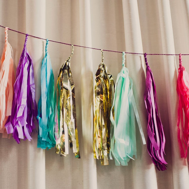 Festive tassels made a cheery addition to the wall behind the dessert table.