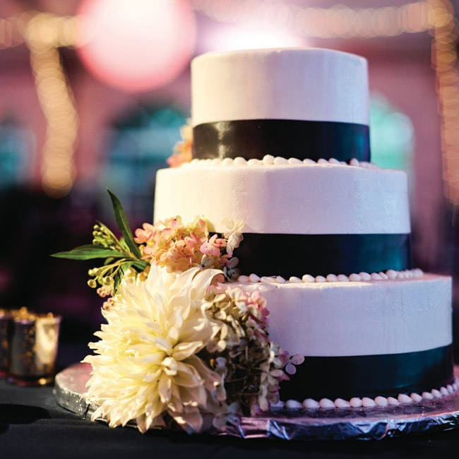 The wedding cake was a simple, white frosted, three-tiered cake with gray satin ribbons wrapped around the bottom of each layer. Fresh flowers cascaded down the side.