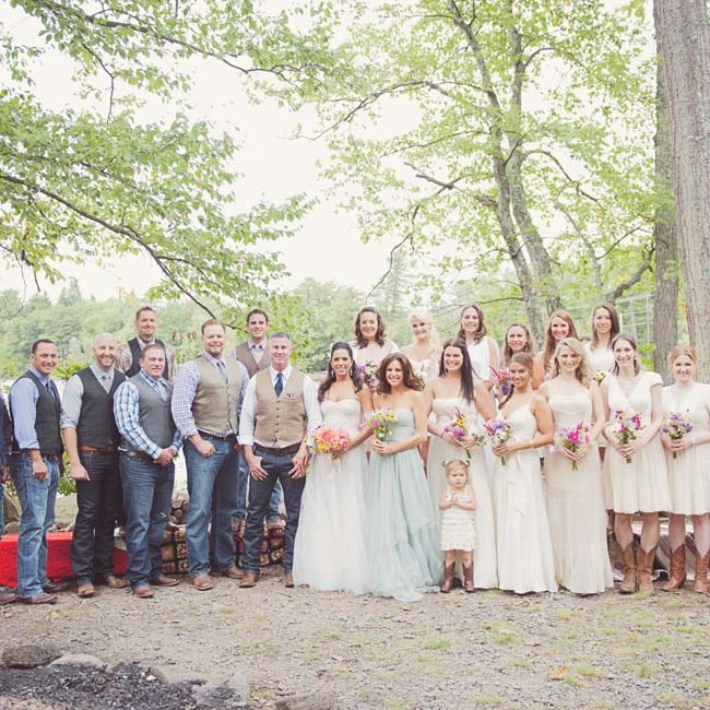 To go with the wedding's casual, country vibe, the groomsmen wore dark jeans, button-down shirts, plaid shirts, brown boots and their own vests. The girls wore ivory festival style dresses in a variety of styles and paired them with brown cowboy boots.