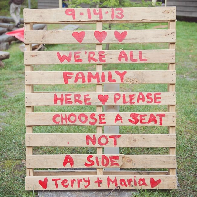 "The couple used a wood pallet for their welcome sign, painting ""We're all family here - please choose a seat not a side"" on the planks in red paint."