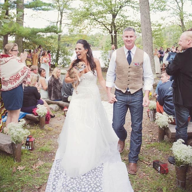 The aisle was lined with airy white fabric with a leaf motif, bunches of baby's breath and Queen Anne's lace arranged in distressed tin pots and red camping lanterns for a rustic, camp-inspired vibe.