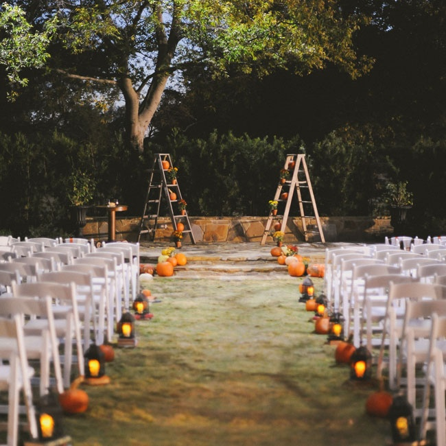 The ceremony took place outside of a barn, beneath two oak trees. The stone altar was decorated with rustic ladders, pumpkins and mums for a vintage look.