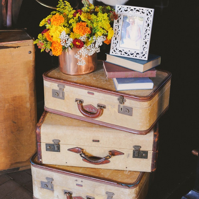 A variety of vintage pieces, including a stack of suitcases, were on display at the reception. Topped with old books and a colorful arrangement of flowers, the vignette added visual interest to the space.