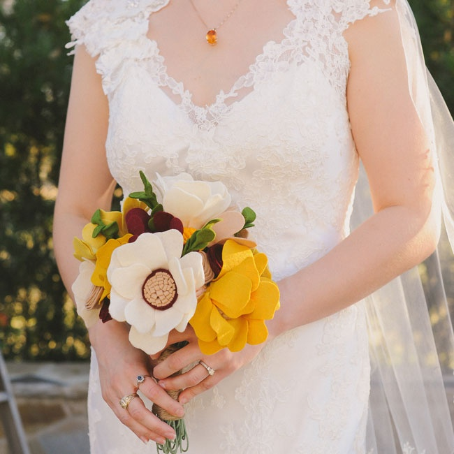 The bright fall colors in Shannon's felt bouquet popped against her white lace bridal gown.