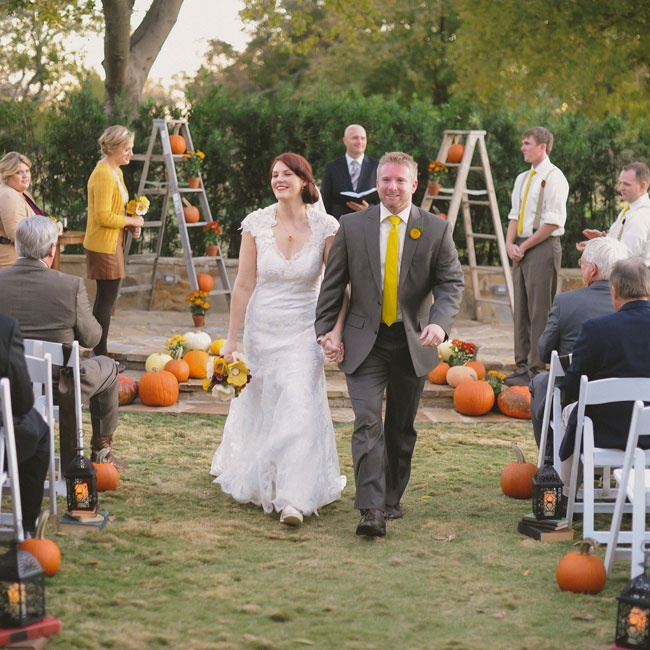 A variety of pumpkins, lanterns and old books decorated the aisle at the outdoor ceremony.