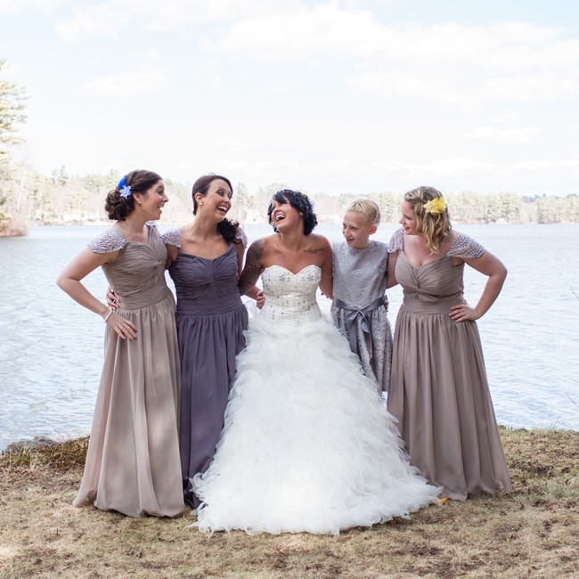 For her bridesmaids, April chose floor-length gowns in dark gray and champagne. The gowns had ruched sweetheart bodices and elegant pearl cap sleeves with pearl bracelets and earrings to tie the look together. Each girl also wore a colorful floral hair accessory and matching shoes in the colors of Slytherin, Ravenclaw and Hufflepuff.