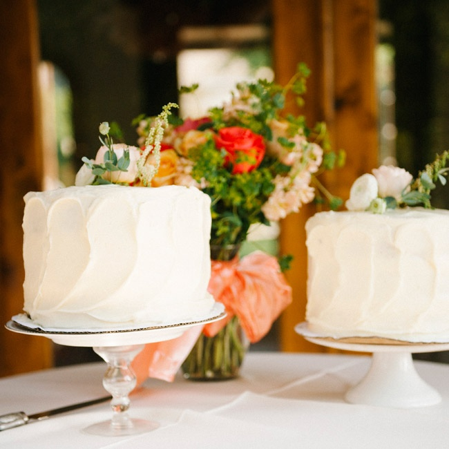 Ivory ranunculuses and eucalyptus leaves topped the simple one-tier buttercream cakes.