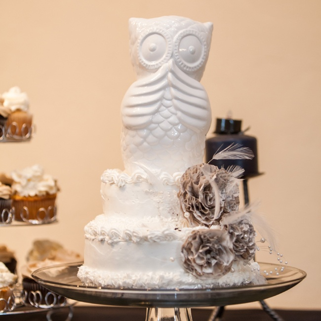 Jordan's grandmother made the two-tier vanilla cake with buttercream frosting. They decorated the cake with an owl cake topper and handmade paperback flowers.