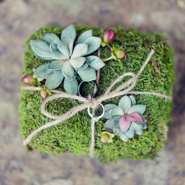 The ring pillow was made from moss and was decorated with succulents, hypernicum berries and a twine bow.