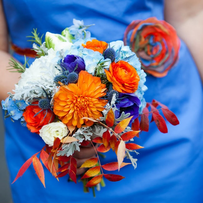 PoppyStone Floral Designs added colorful fall leaves to the bridesmaids' orange and blue bouquets of ranunculus, hydrangeas and roses.