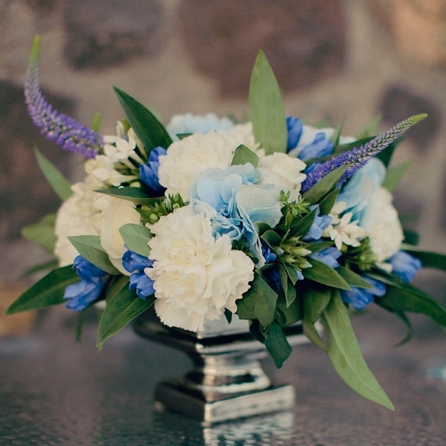 The couple paired white carnations with purple delphinium and blue hydrangeas to create a pop of color to the reception.