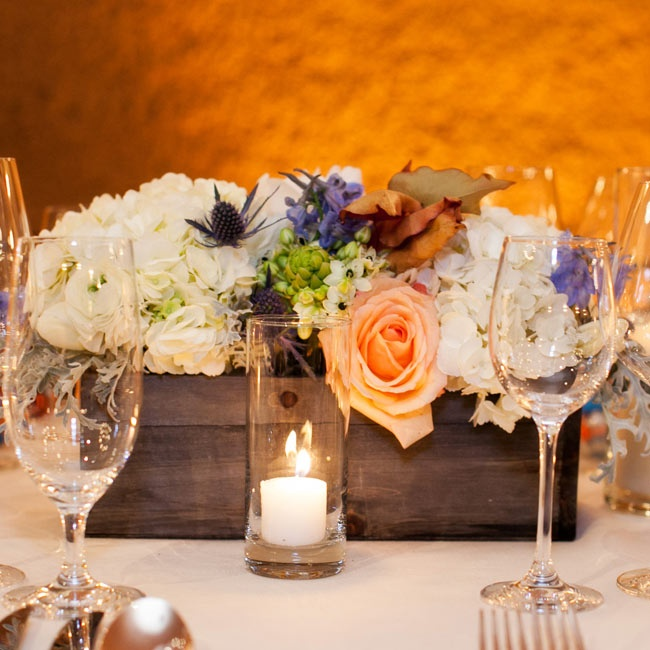 The centerpieces were arrangements of roses, hyacinth, hydrangea and fall leaves in rustic wooden boxes.