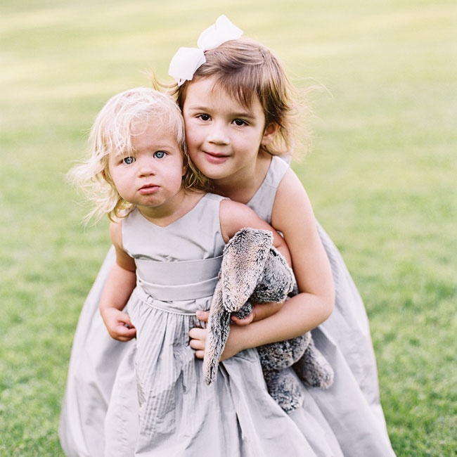 The flower girls wore full skirted gray dresses and white bows in their hair for a classic look.