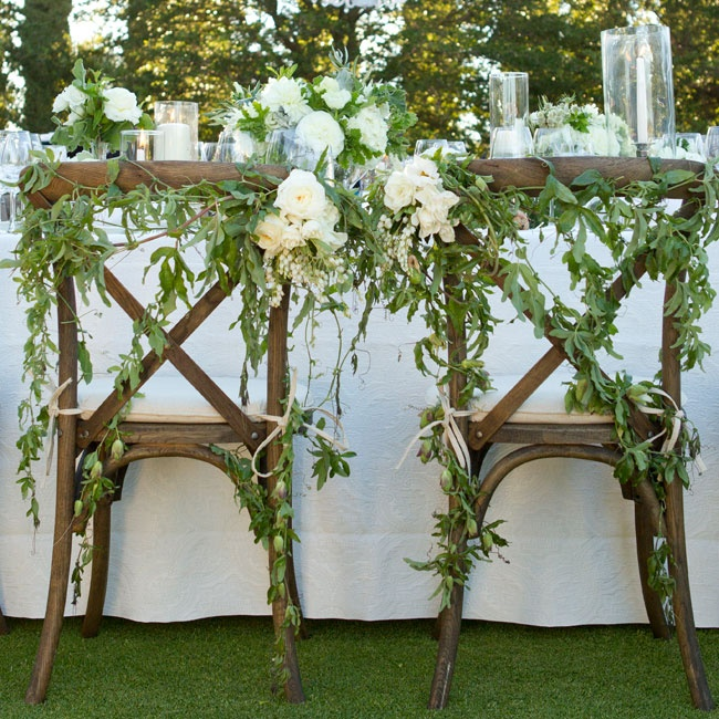 The newlyweds' chairs were draped in leafy vines and ivory roses.