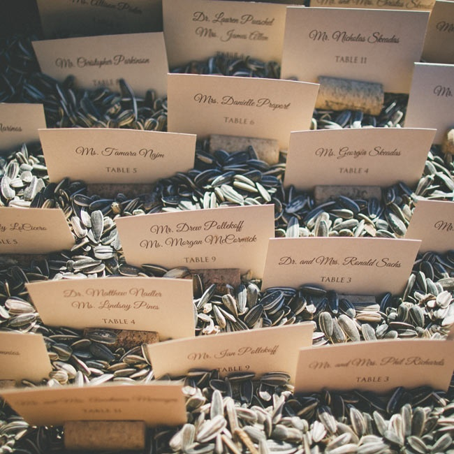 Simple escort cards were placed in wine corks and displayed in a bed of sunflower seeds.