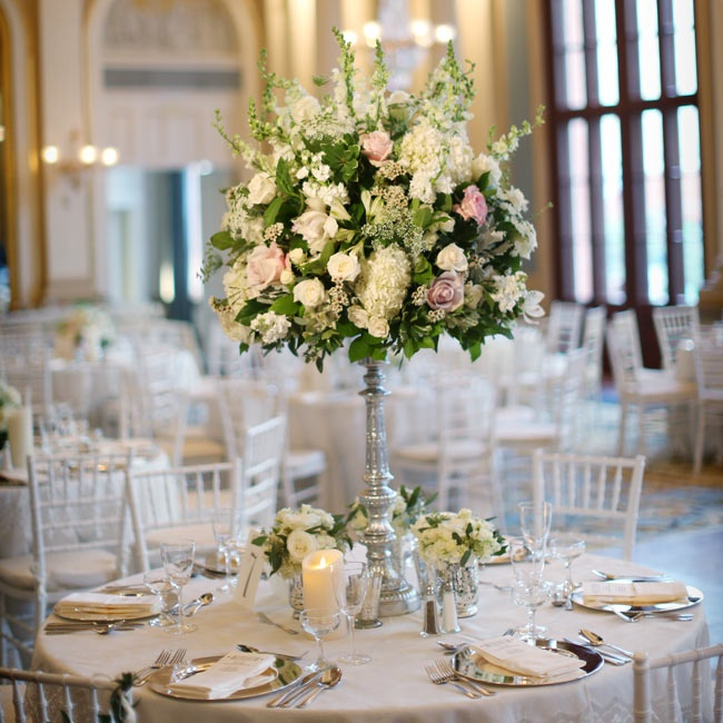 Cream silk linens were topped with lush, tall arrangements of hydrangeas, roses, stock and wax flowers.