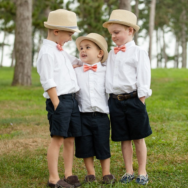The three boys in the wedding party wore navy shorts, which button-down shirts and coral bow ties. Adorable fedoras from J.Crew topped off their look.