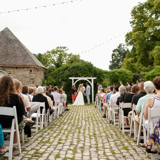 The ceremony was held outside on a cobblestone courtyard. The couple exchanged vows under a white wooden arch in front of lush vines and flowers.