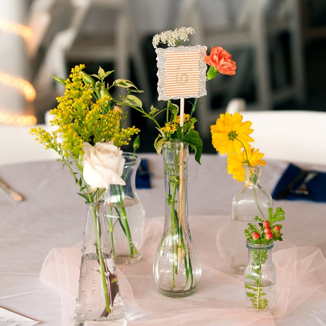 """Our centerpieces were simple,"" says Kate. She collected various glass vases and filled each with flowers from her florist's garden or from the farmers market. Table numbers made from scrapbook paper completed the look."