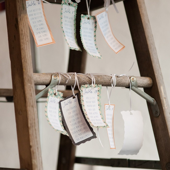 Small, scrapbook paper tags with seating assignments hung from the rungs of an old ladder.