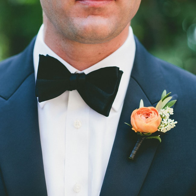 A bright orange ranunculus popped against Aaron's navy tuxedo.