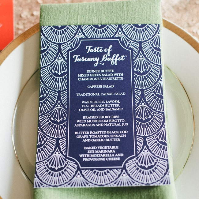 The navy blue menus used the same art deco print as the couple's invitations. The menus were placed on soft green table linens and gold-rimmed china.