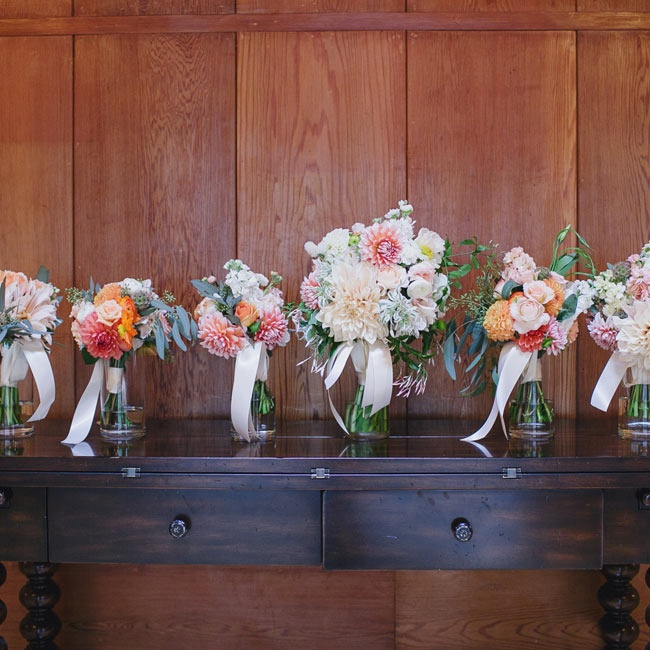 The bride and her bridesmaids carried matching bouquets of light pink, orange and white flowers.