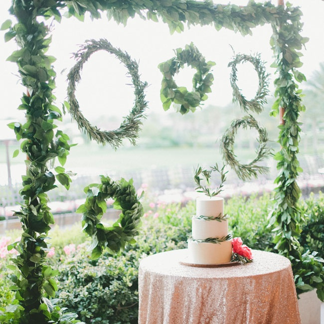 A trellis decorated with lush leafy garlands and fresh green wreaths stood behind the cake table. The unique backdrop complemented the cake's decorative olive leaf accents and tied into the day's Italian-inspired look.