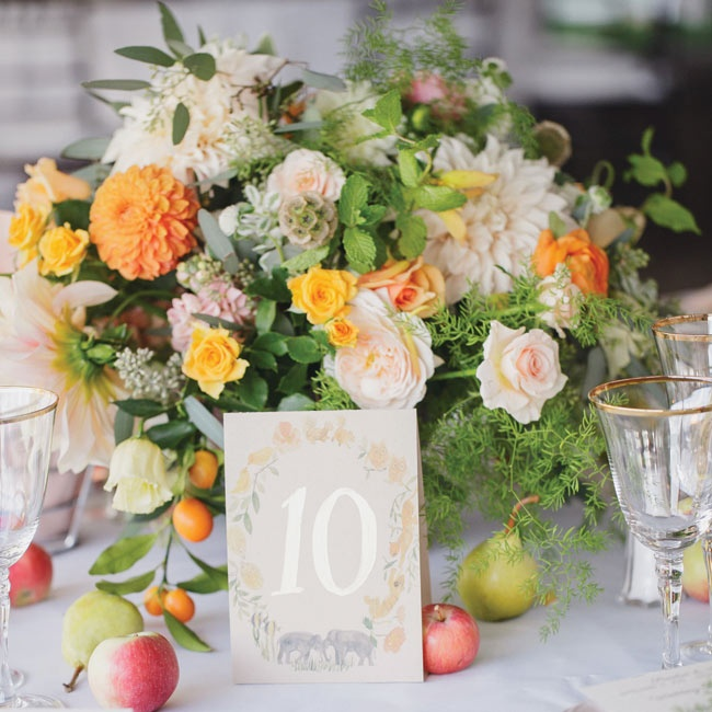 Orange and white dahlias and roses mixed with pears and apples in the intricate centerpiece arrangements at the reception.