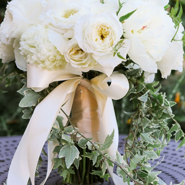 Garden roses, peonies and garden roses in a soft shade of ivory filled Sara's bridal bouquet. Cascading ivy framed the bouquet, adding a whimsical touch and hint of color.