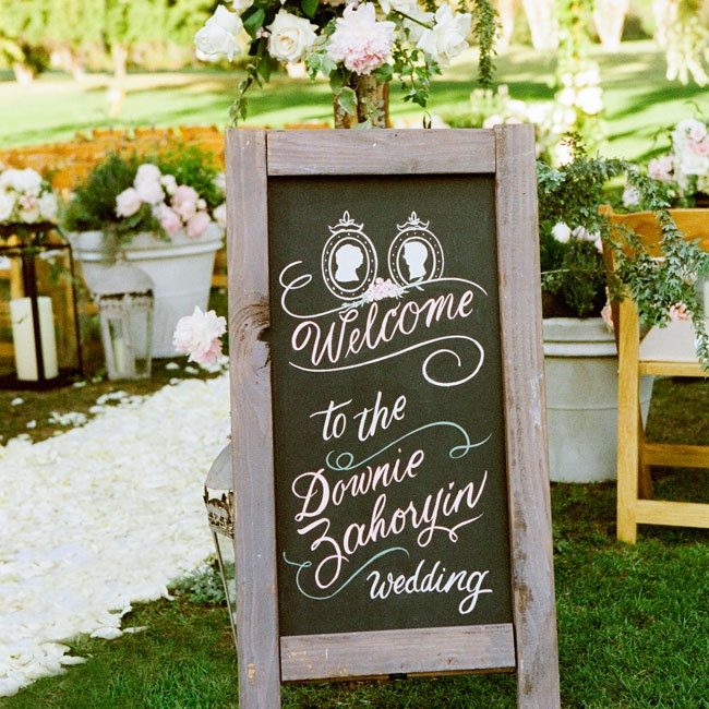 A wood-framed chalkboard sign welcomed guests to the ceremony. The board had a romantic, Victorian feel with framed silhouettes and curly calligraphy.