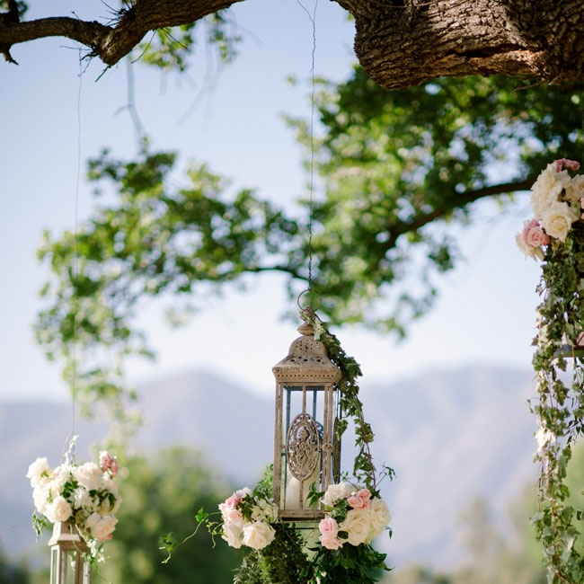 To give the ceremony setting a romantic feel, the couple hung antique lanterns draped with cascades of ivy and bunches of pink and white flowers from an old oak tree where the ceremony would take place.