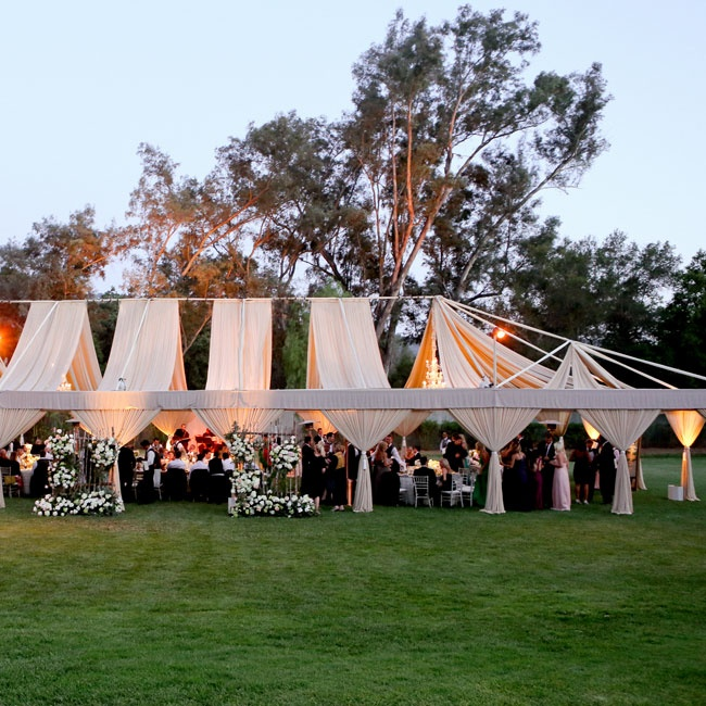 The open air reception tent was draped with airy nude-colored fabric, perfect for the wedding's elegant, romantic vibe.