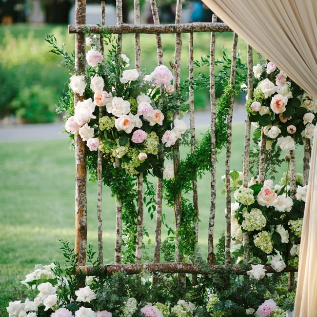 Next to the reception tent stood birch trellises covered in arrangements of pink, peach and ivory garden roses, peonies and hydrangeas.