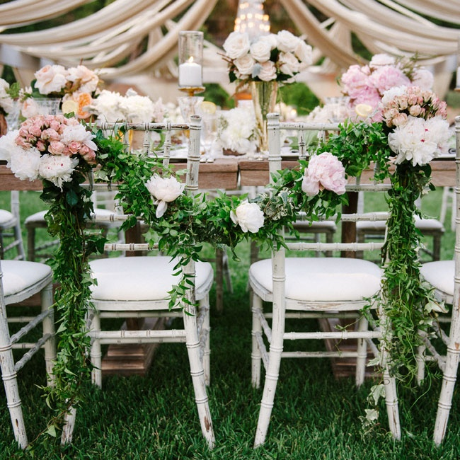 The newlyweds' chairs were decorated with a fresh green garland and bunches of pink roses and peonies.