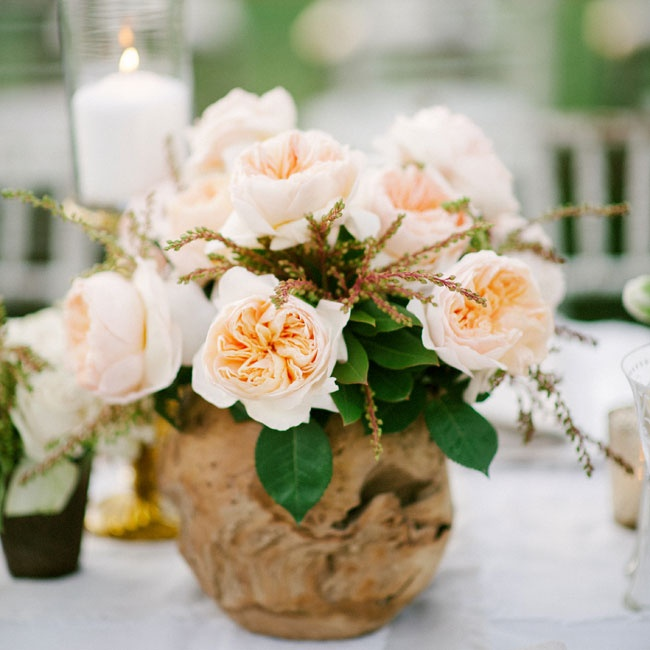 The peach garden rose centerpieces were arranged in beach wood vases adding a rustic element to the tablscapes.
