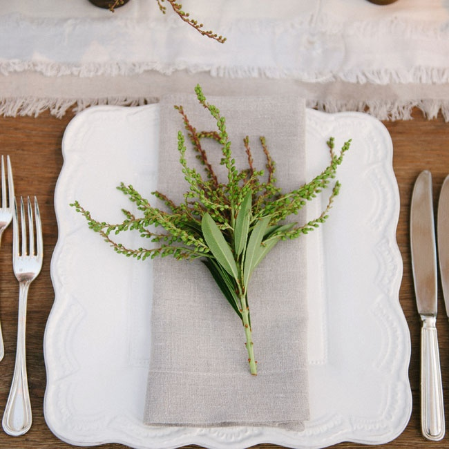 White scallop-edged china was set with simple neutral linen napkins and sprigs of lily of the valley.