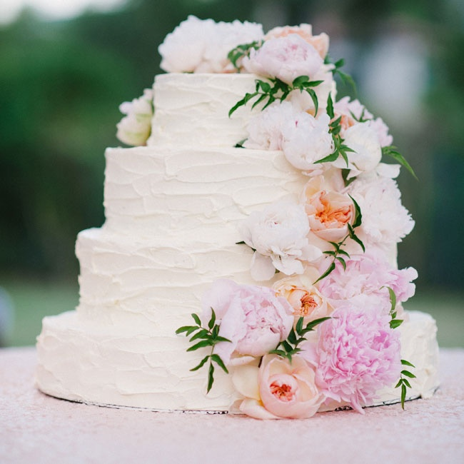 The four-tier buttercream cake was decorated with a cascade of pink peonies and garden roses.