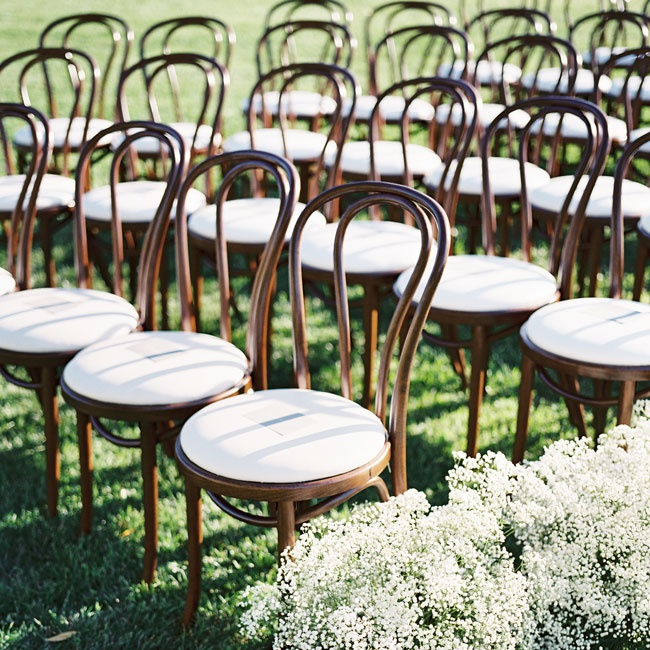 The couple chose bistro chairs for the ceremony. The aisles were lined with simple bunches of baby's breath.