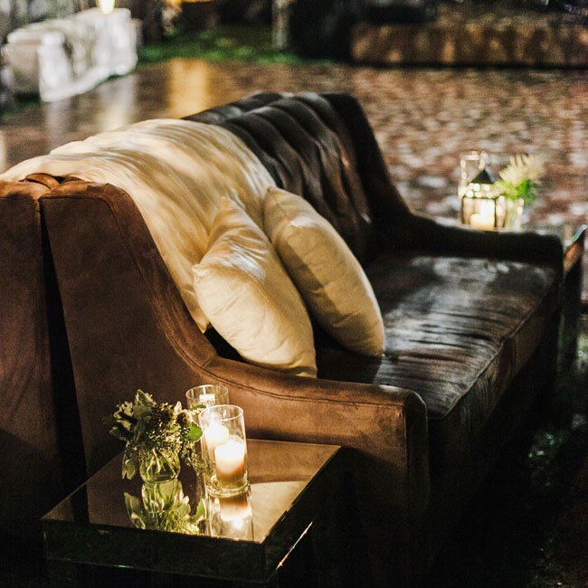 Brown suede settees draped with cream-colored throw blankets and pillows gave the lounge area a rustic chic flair, while warm candle light added ambient charm.