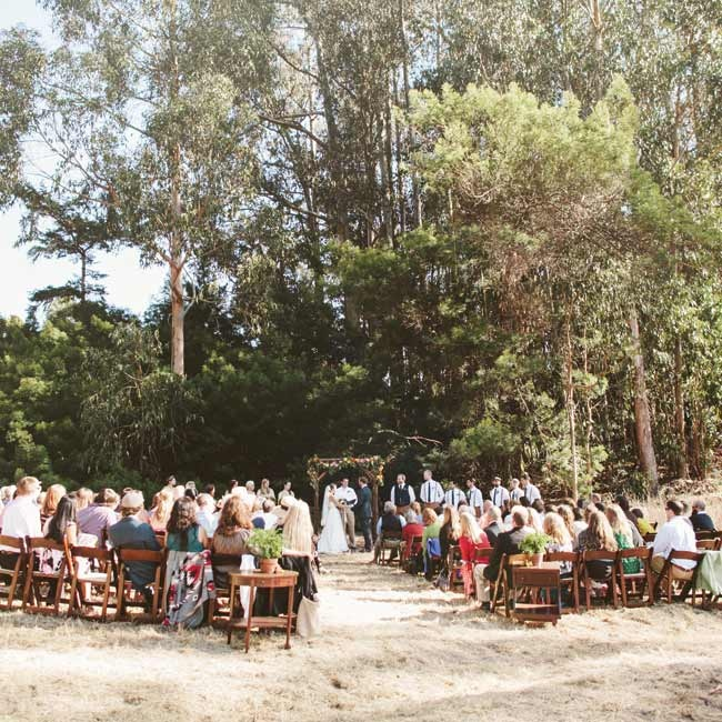 The ceremony took place in the outdoors against the backdrop of a wooded forest.