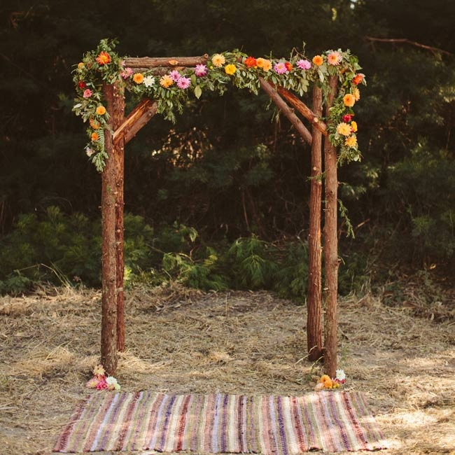 The couple exchanged vows beneath this wooden ceremony arch draped with a floral garland.