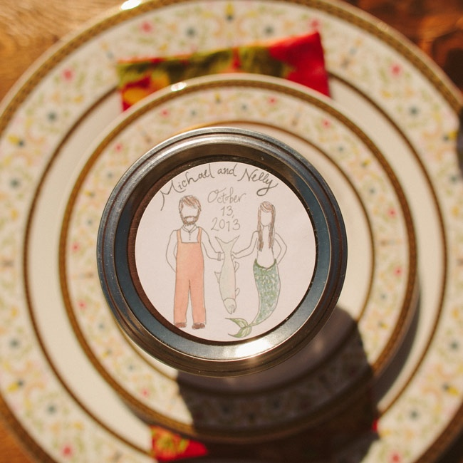A hand drawn illustration of the couple personalized the couple's favors and sat atop the china at the reception tables.