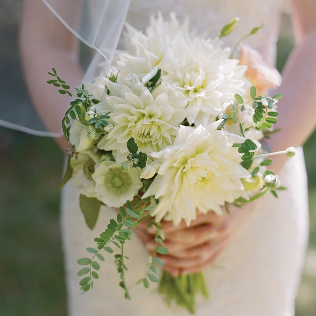 "Caitlin's green and white bouquet of dahlias was wrapped in the lace from her mother's wedding dress. She also pinned both of her grandmothers' engagement rings as well as her great grandmother's locket to the bouquet for ""something old."""