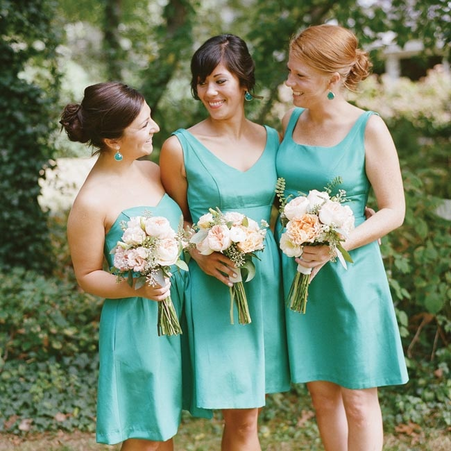 Caitlin's bridesmaids wore knee-length gowns in the same teal-colored fabric with the neckline of their choice. They carried Juliet roses, ranunculus and dahlias in soft shades of pink and orange to complement their dresses.