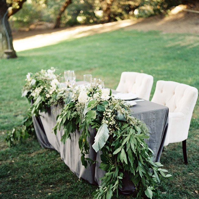 The couple's sweetheart table stood at the head of the reception. The table was decorated with an opulent green garland and set with two plush white arm chairs.