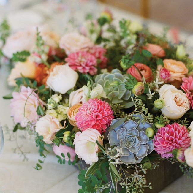 Dahlias, garden roses, ranunculus and succulents were placed inside wooden boxes on the guest tables.