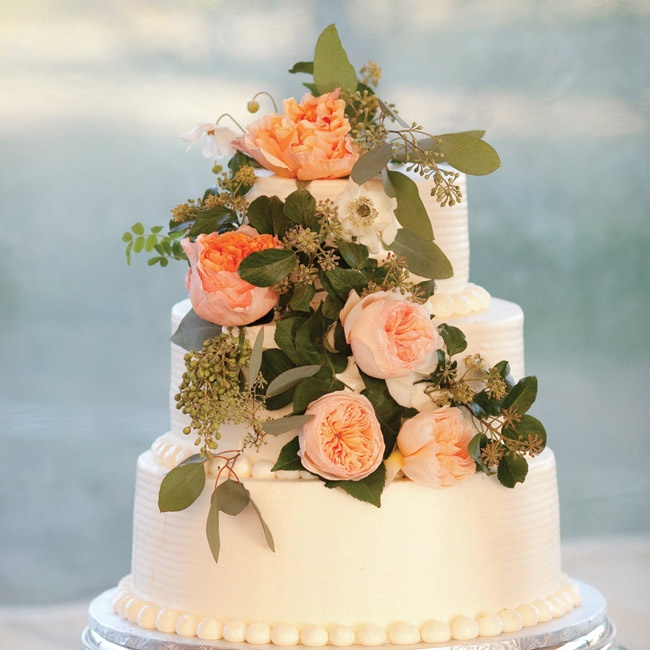 The three-tier vanilla cake with fresh strawberry filling was iced in buttercream and topped with Juliet roses.