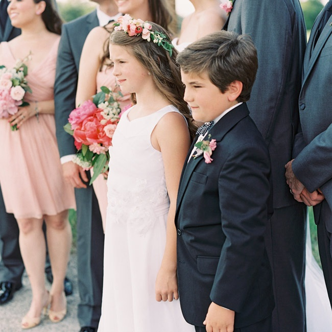 The flower girl wore a white chiffon dress and carried a basket of white rose petals to sprinkle in the aisle, while the ring bearer wore a black suit and carried a white ring pillow.