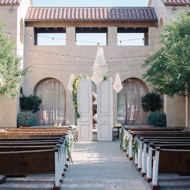 The ceremony took place in the courtyard at Serra Plaza. Vanessa and Mike used vintage doors, church pews and chandeliers to transform the space into an open-air chapel.